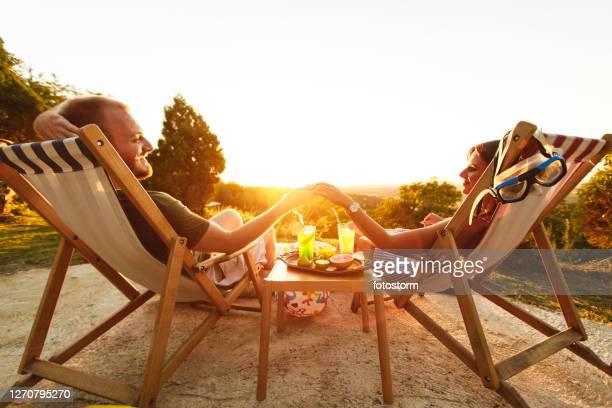 jeunes couples appréciant la journée d'été sur des chaises de pont avec des cocktails et des gonflables - transat photos et images de collection