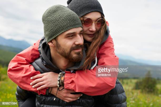 young couple enjoying summer holiday in the mountains - red jacket stock pictures, royalty-free photos & images