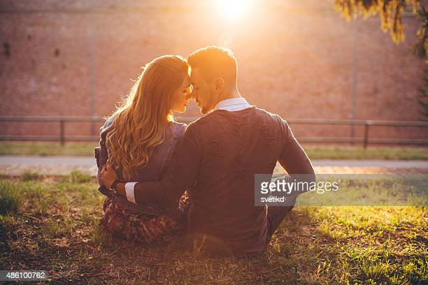 Young couple enjoying sunset in park.