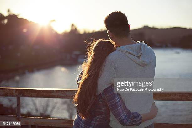 young couple enjoying sunset - teenage couple stock photos and pictures