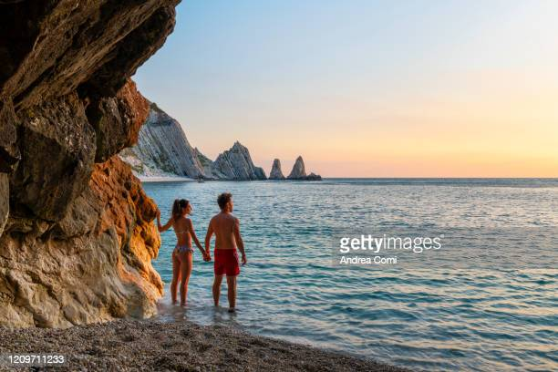young couple enjoying the sunrise at two sisters beach (le due sorelle). conero, italy - mittelmeer stock-fotos und bilder