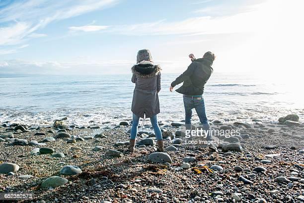 A young couple enjoying the sunshine on the beach at Porthmadog