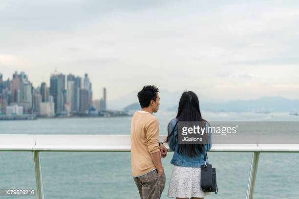 Young couple enjoying the view of the Hong Kong city skyline from Harbour City
