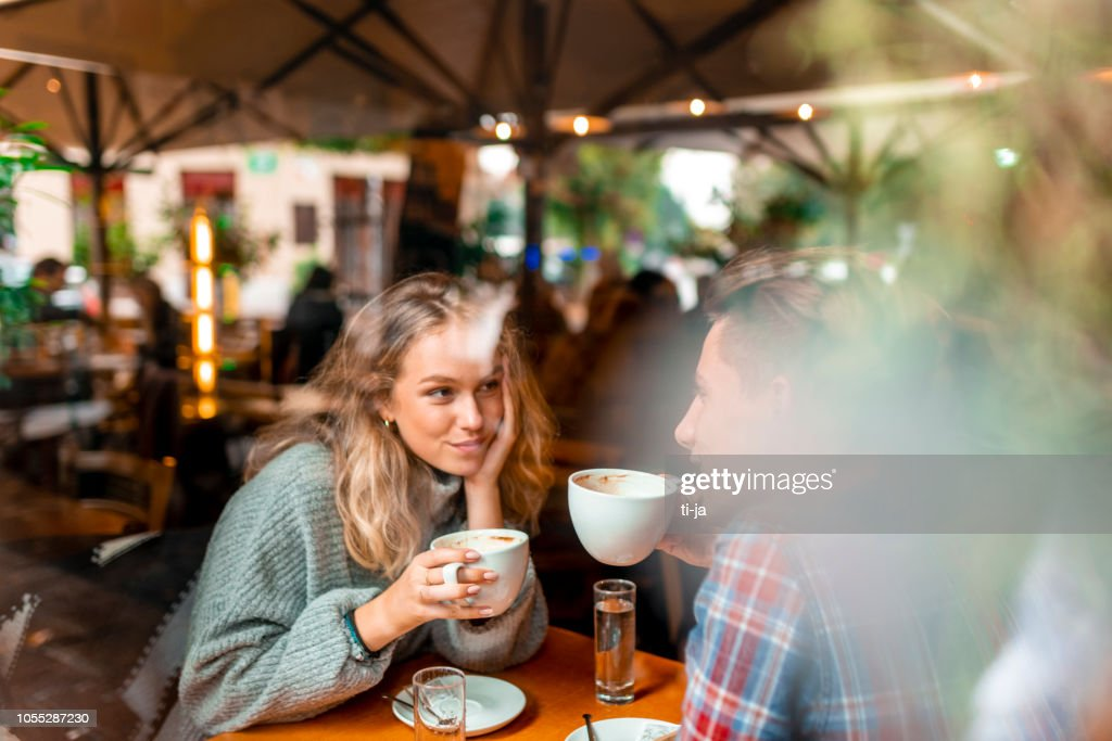 Young couple enjoying their coffee in a bar : Stock Photo
