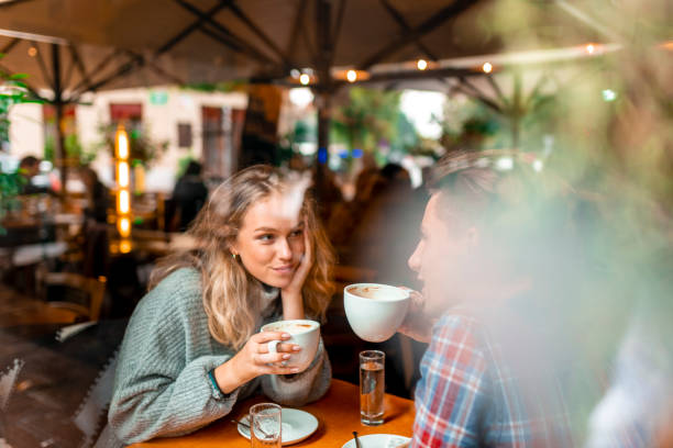 young couple enjoying their coffee in a bar - couples romance stock pictures, royalty-free photos & images