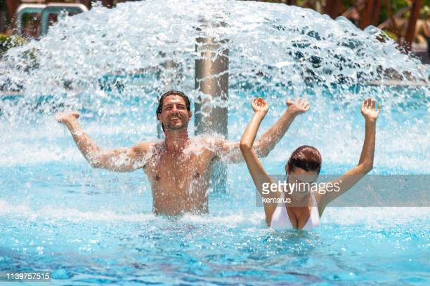 Young couple enjoying under water fountain