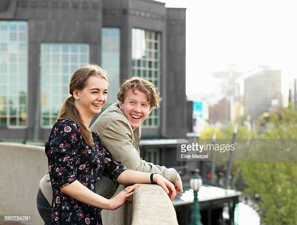 Young couple enjoying view from terrace, Melbourne, Victoria, Australia