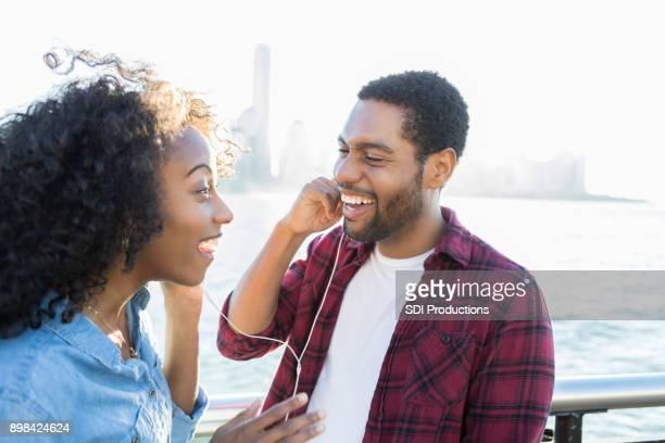 Joven pareja disfruta de compartir los auriculares en el muelle de la ciudad