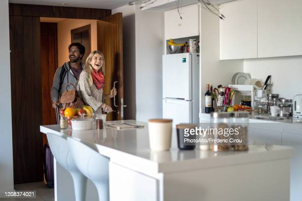 young couple entering new home - entering stock pictures, royalty-free photos & images