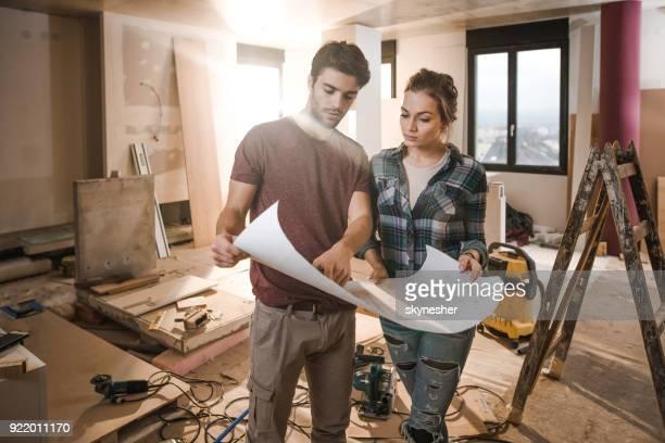 Junges Paar Baupläne selbst auf Baustelle in ihrer Wohnung zu prüfen.