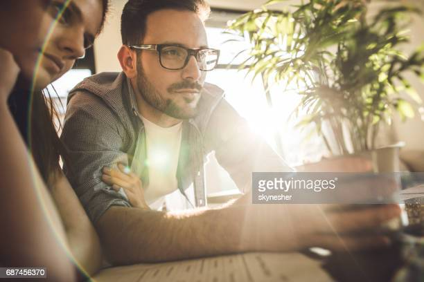young couple examining growth of a potted plant. - money tree stock photos and pictures