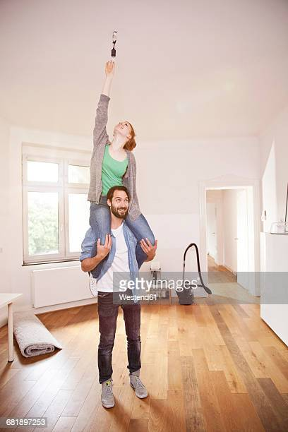 Young couple exchanging a light bulb in their new apartment together