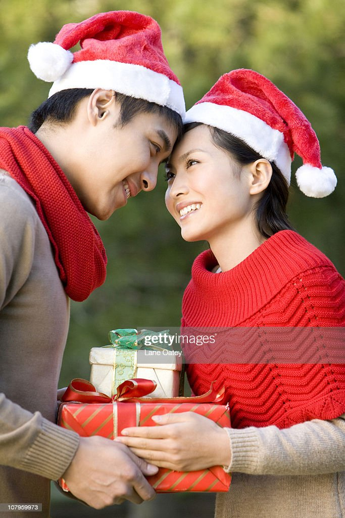 young couple exchanging christmas gifts stock photo