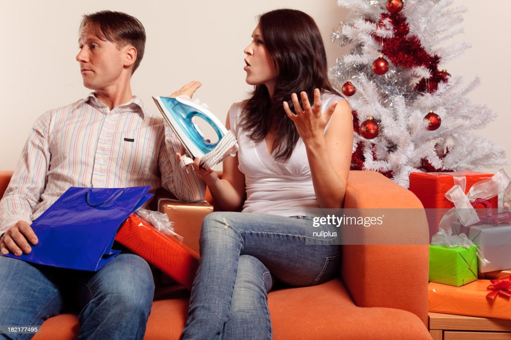 young couple exchanging christmas gifts series stock photo