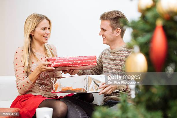 Young couple exchanging christmas presents in living room