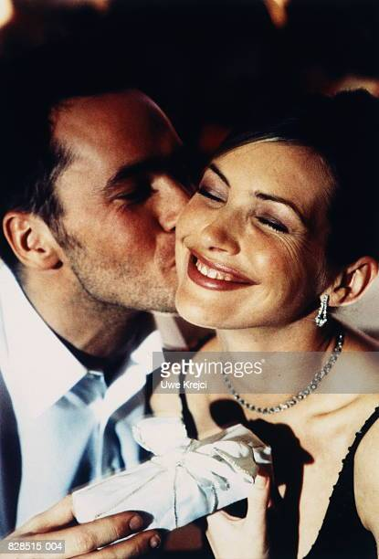 young couple exchanging gifts, man kissing woman on cheek, close-up - amado carrillo fuentes fotografías e imágenes de stock