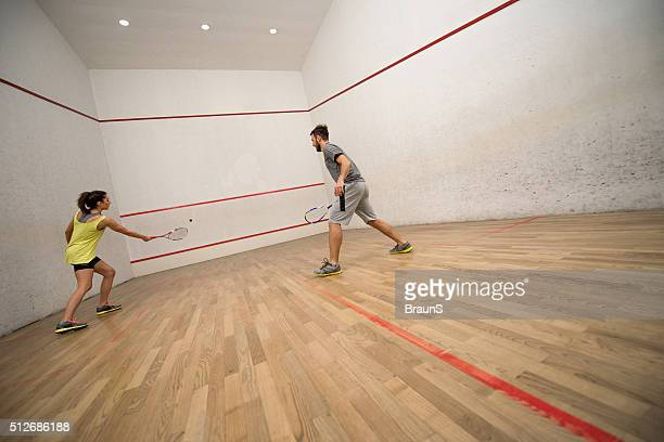 Young couple exercising squash on a court.
