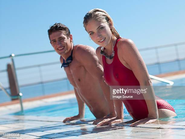 Young couple exiting swimming pool