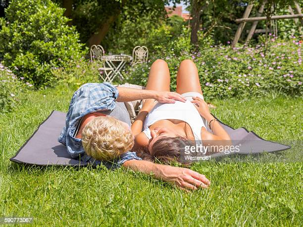 Young couple expecting baby, lying in garden