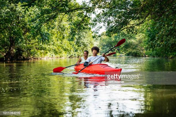 young couple exploring river in kayak - paddling stock pictures, royalty-free photos & images