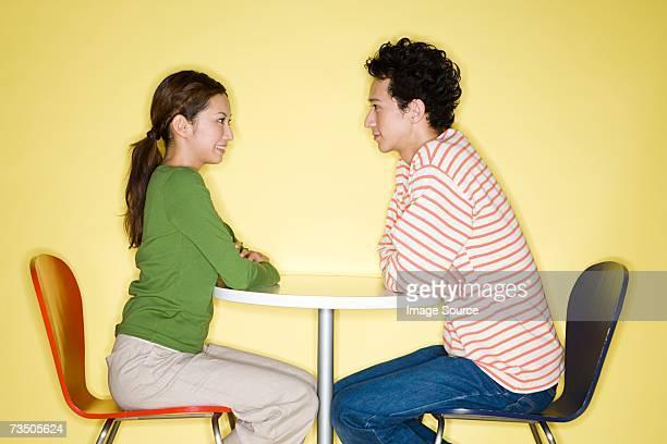 若いカップル顔、顔、顔のテーブル
