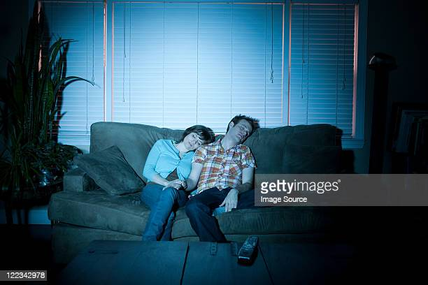 young couple fallen asleep in front of tv - couple sleeping stock pictures, royalty-free photos & images