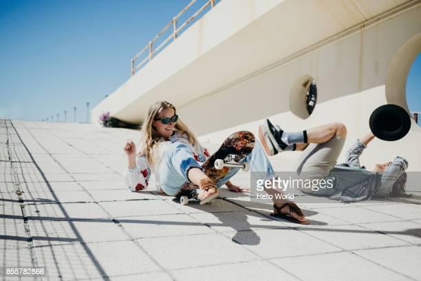 Young couple fallen off skateboard