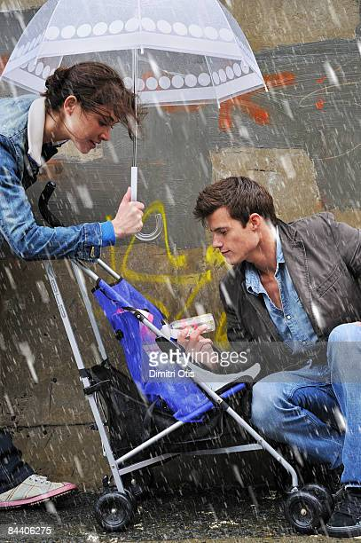 young couple feeding baby in the rain