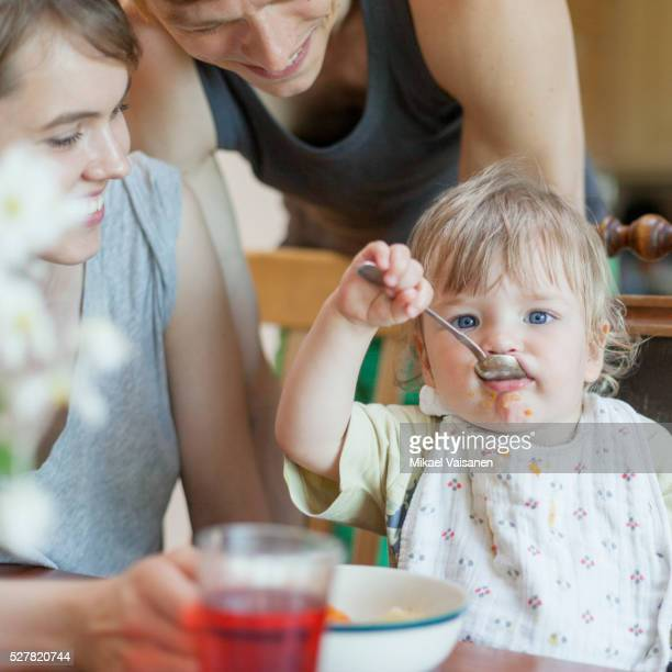 Young couple feeding little boy (12-23 months)
