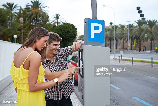 young couple feeding parking meter - parking meter stock photos and pictures