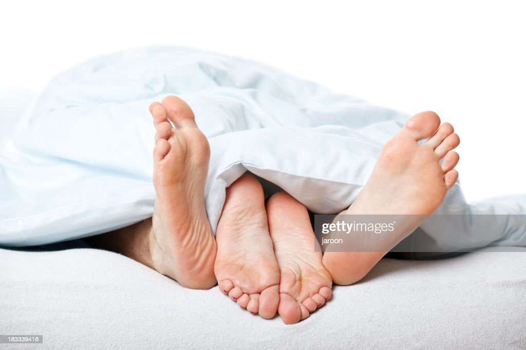 young couple feet in bed : Stock Photo