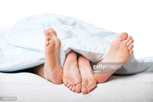 young couple feet in bed