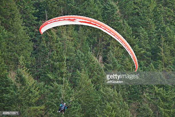Tandem Paraglider Flying by the Trees