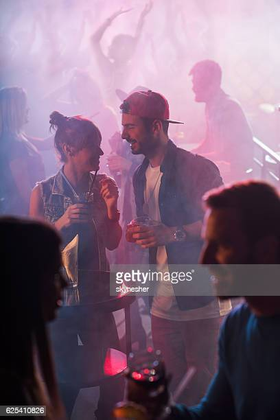 Young couple flirting while spending night in a club.