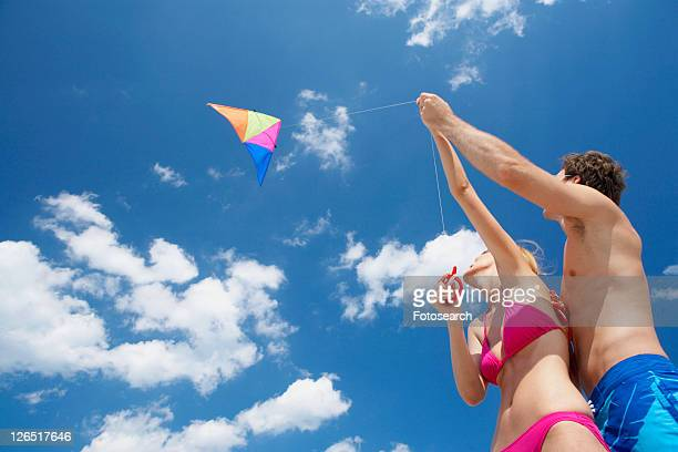 Young couple flying kite (low angle view)