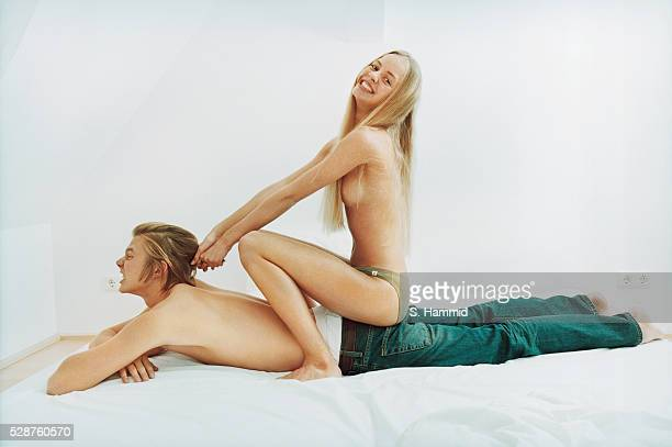 Young couple fooling around in bed