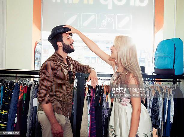 young couple fooling around in clothing store - the past stockfoto's en -beelden