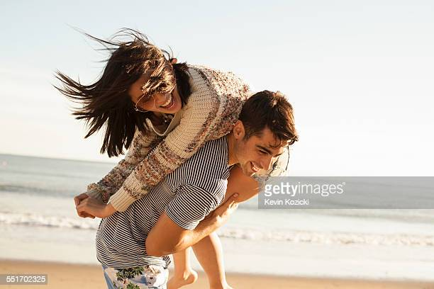 young couple fooling around on beach - coppia di giovani foto e immagini stock