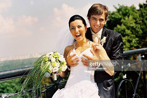 young couple fooling around on their wedding day - wijzen handgebaar stockfoto's en -beelden