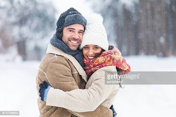 young couple freezing and embracing in snow forest - winter coat stock pictures, royalty-free photos & images