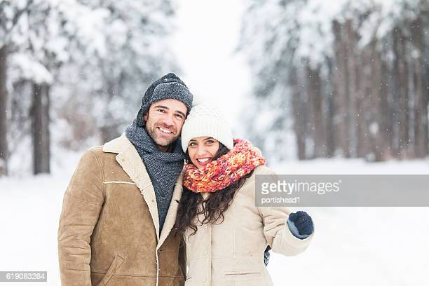 Young couple freezing and standing close in snow forest