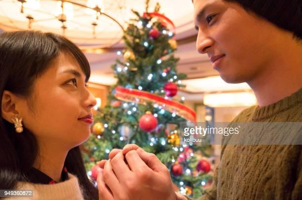 クリスマス ツリーの前で若いカップルを見つめる