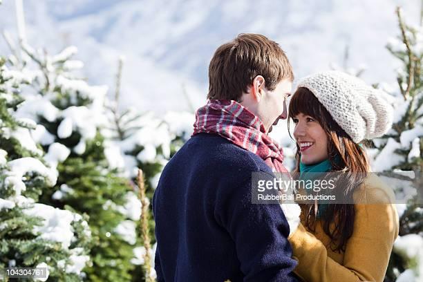 Joven Pareja contrayendo un árbol de Navidad en la nieve