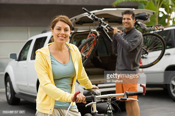 Young couple getting bikes from back of car