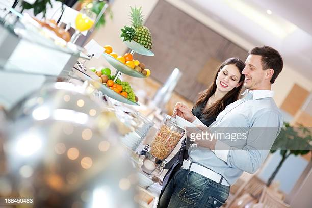 Young couple getting breakfast at a hotel buffet