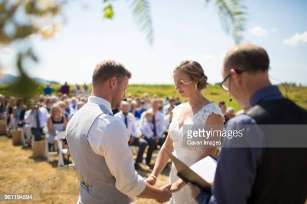 young couple getting married by priest during sunny day - wedding vows stock pictures, royalty-free photos & images