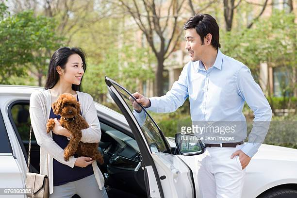 Young couple getting out of car with their pet dog