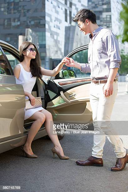 Young couple getting out of their car