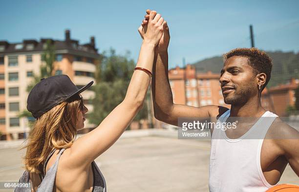 Young couple giving high five on basketball court
