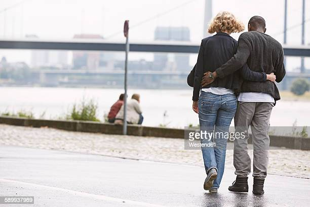 Young couple going for a walk at the riverside